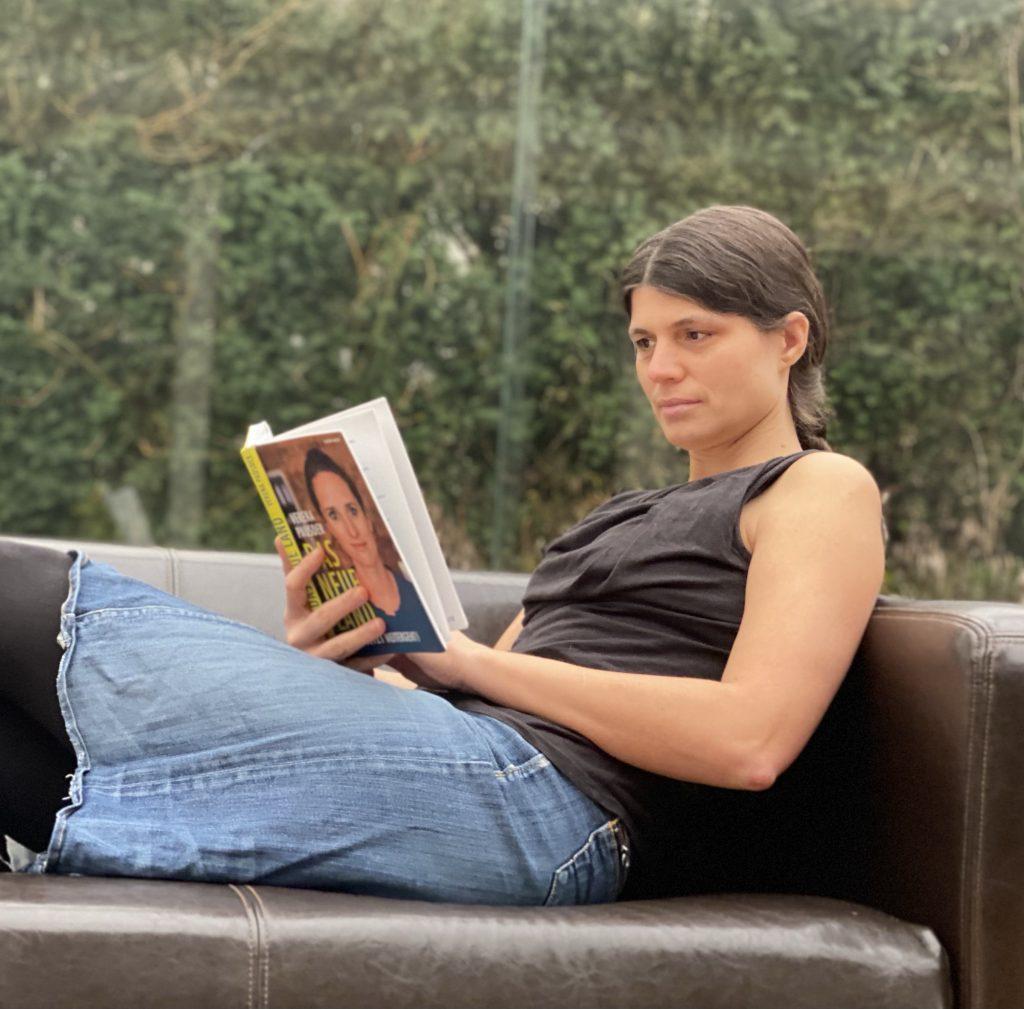 Veronika sitzt lesend auf dem Sofa.