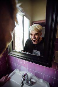 Mensch brüllt wütend in den Badezimmer-Spiegel
