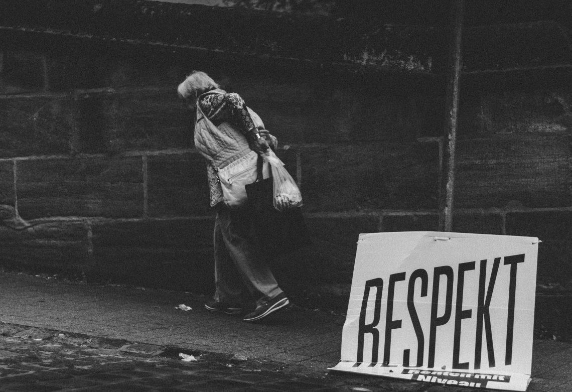"""Ein Schild mit der Aufschrift """"Respekt"""" ist zu Boden gefallen, eine Person geht achtlos daran vorbei."""