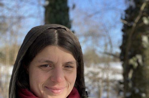 Veronika im Winterwald in die Kamera schauend