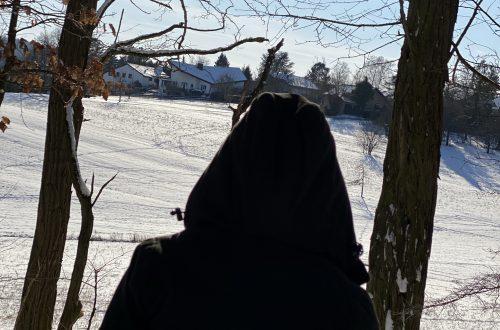 Veronika sitzt in der Winterlandschaft und schaut auf die Wiese