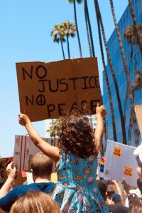 Gerechtigkeit in die Welt bringen, das ist mein Antrieb. Auf dem Bild: Ein Kind mit einem Schild