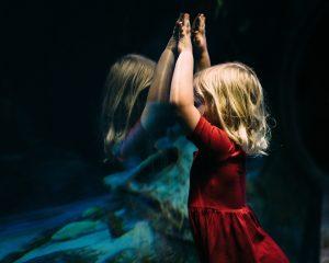 Schon in der Kindheit erleben wir immer wieder Situationen, die den Schluss nahelegen, dass es besser ist, sich nicht wirklich zu zeigen. (Bild von Bekah Russom) Zu sehen ist ein Kind in rotem Kleid, das sich gegen eine Glasscheibe lehnt und darin sein Spiegelbild betrachtet.