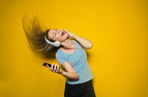 Wildes Tanzen zu lauter Musik kann eine tolle Energiequelle sein. Auf dem Bild: Singende, tanzende Person vor gelbem Hintergrund.