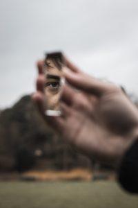 Wir sehen immer nur Bruchstücke der anderen, selbst bei direkten Begegnungen. Lasst uns mutiger werden in dem, was wir von uns zeigen. (Bild von Alex Motoc). [Zu sehen ist eine Hand, die eine Spiegelscherbe hält, in der ein Auge zu sehen ist.]