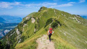 Dank meiner Kinder ist meine persönliche Entwicklung deutlich zielgerichteter geworden. Danke dafür! Im Bild ist eine Person mit Wanderrucksack zu sehen, die auf einem Berggrat entlang läuft, hin zu einem weitern Gipfel.