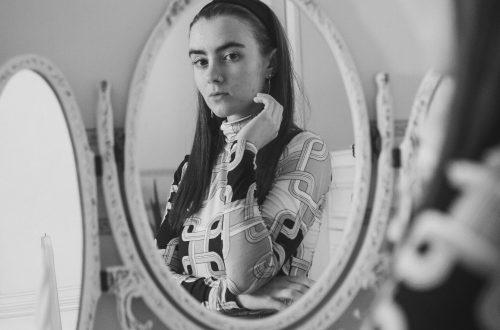 Viele von uns haben gelernt, dass Sichtbarkeit eher gefährlich ist. Und doch ist es wichtig uns zu zeigen. Zu sehen: weiblich gelesene Person betrachtet sich im Spiegel, Blick wirkt kritisch.