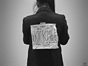 """Hass im Netz hält vor allem Frauen oft davon ab sich im Netz zu zeigen. Gemeinsam können wir das ändern. (Bild von Ilayza Macayan) Es ist der RÜcken einer Person zu sehen. Dort ist ein Zettel mit """"Kick me!"""" und verschiedenen Zuschreibungen wie """"fat"""" """"ugly"""" """"thin"""" zu lesen"""