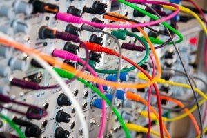 In der modernen Welt hängt alles zusammen. Wie genau diese Zusammenhänge sind, können wir oft höchstens im Nachhinein verstehen. (Bild von John Barkiple) Zu sehen: bunte KAbel, die scheinbar wild durcheinander in Buchsen stecken.